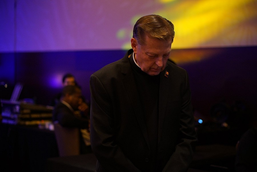 100th Anniversary Gala | Father Michael Pfleger bows his head as Father Thulani prays | photo by Mack Julion