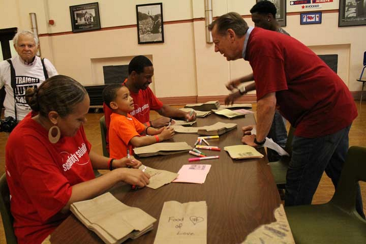 Day of Service on July.9.2016. _ Father Pfleger speaks to a young member making lunch bags for the homeless at St. Sabina Academy _ photo by Chinta Strausberg